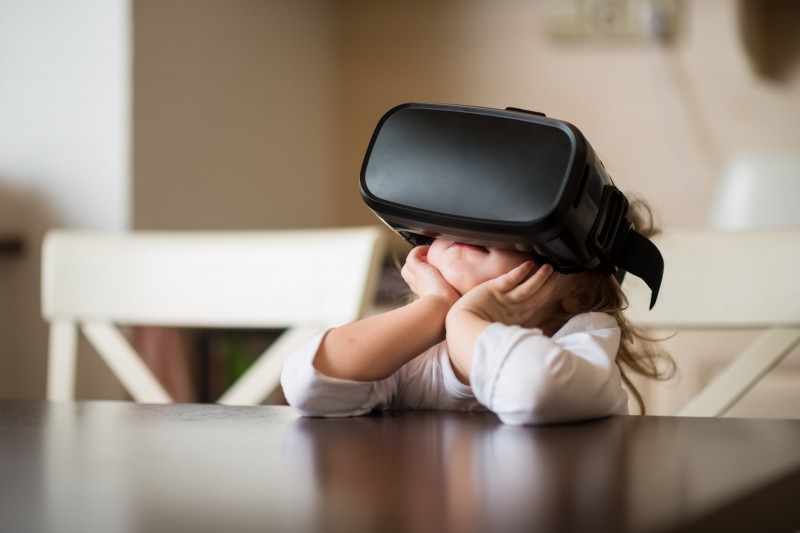 a little girl sitting at the table with a virtual reality headset on