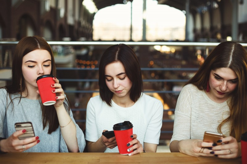 3 teenage girls sitting in a coffee shop on their own phones.