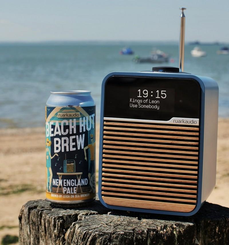 Ruark Audio R1 Beach Hut Blue alongside a can of Beach Hut Brew, New England Pale Ale