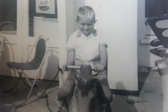 A young Jim on a rocking horse